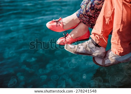 Young couple sitting on the dock by the sea background, feet closeup - stock photo