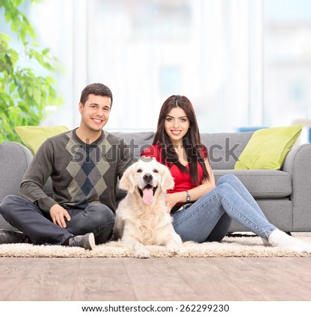 Young couple sitting on the floor with a dog at home shot with tilt and shift lens