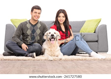 Young couple sitting on the floor with a dog isolated on white background - stock photo