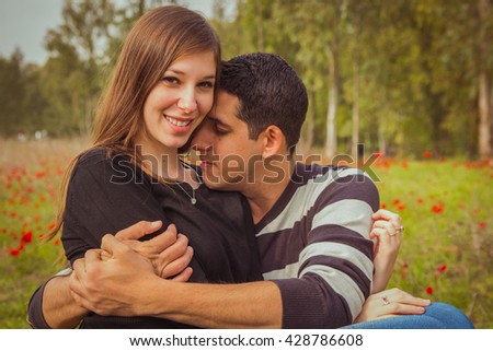 Young couple sitting on the grass in a field of red poppies and smiling at the camera. - stock photo