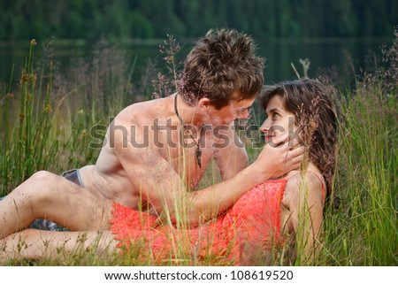 Young couple sitting on the grass on the shore, lost in love