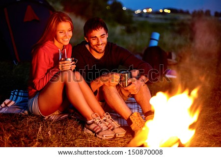 Young couple sitting on the ground and drinking tea while looking at fire - stock photo