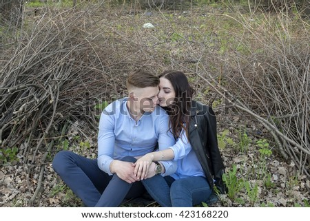 Young couple sitting on the ground and kissing - stock photo
