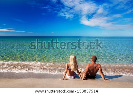 young couple sitting on the sea sand beach and looking at sky - stock photo