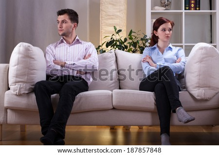 Young couple sitting on the sofa after quarrel - stock photo
