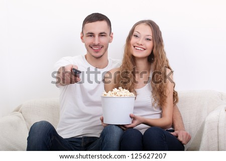 young couple sitting on the sofa eating popcorn and watching  tv