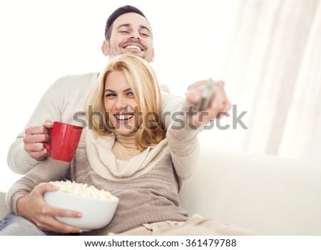 Young couple sitting on the sofa in the living room and watching TV.They are laughing and watching a movie or television. - stock photo