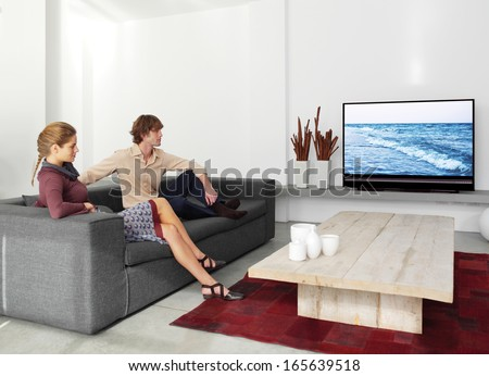 young couple sitting on the sofa watching tv in the living room  - stock photo