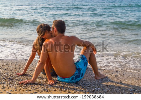 Young couple sitting on wet sand on the beach enjoys a mid summer late afternoon.