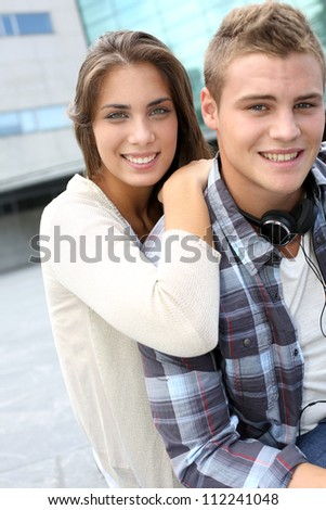 Young couple sitting outside the college building - stock photo