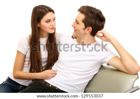 Young couple sitting together isolated on white