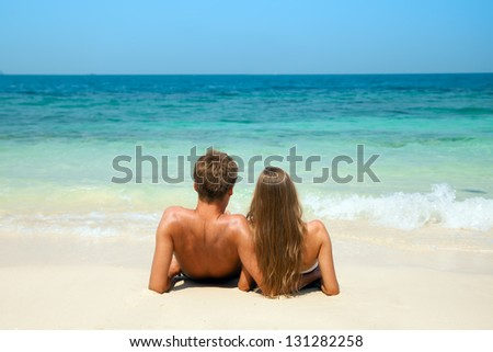 Young couple sitting together on a sand by sea and looking to a horizon