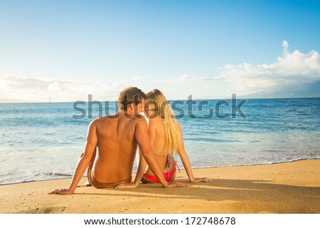 Young couple sitting together on a sandy tropical beach - stock photo