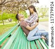 Young couple sitting together on spring  park bench under the cherry blossoms - stock photo