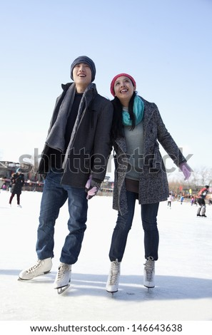 Young couple skating at ice rink - stock photo