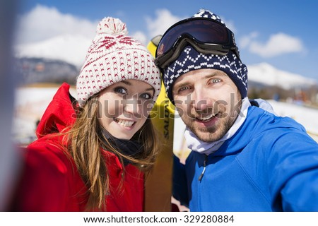 Young couple skiing outside in sunny winter mountains - stock photo