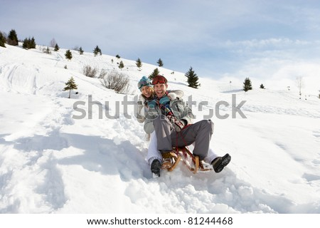 Young Couple Sledding - stock photo