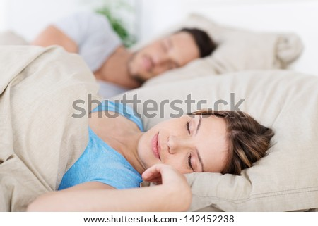 Young couple sleeping in bed having a restful sleep, closeup of the wife - stock photo