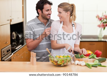 Young couple slicing vegetables in their living room - stock photo