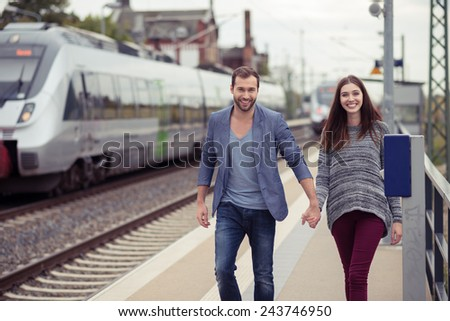 Young couple smiling and holding hands walking down a station platform towards the camera with a train pulled in on the opposite track - stock photo