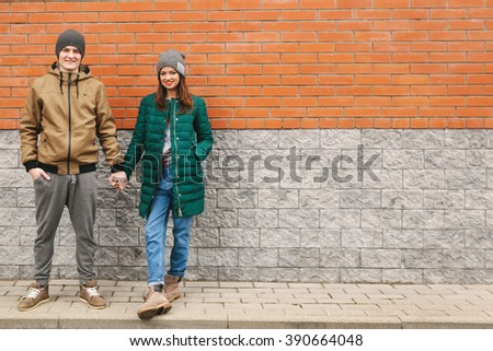 Young couple smiling and holding their hands. Casual clothes, urban, brick background. Copyspace - stock photo