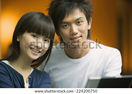 Young couple smiling at camera, head and shoulders, portrait