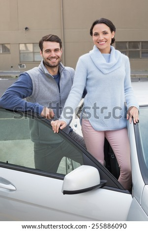 Young couple smiling at camera outside their car