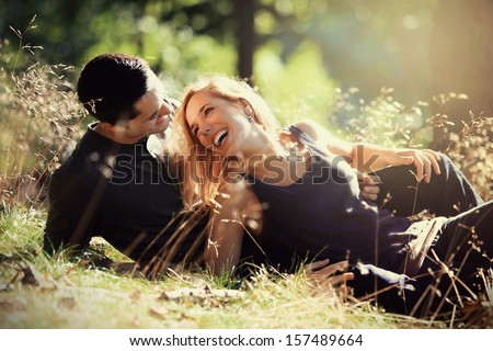 young couple smiling at each other during a romantic date in the forest - strong sunlight - shot against sun - stock photo