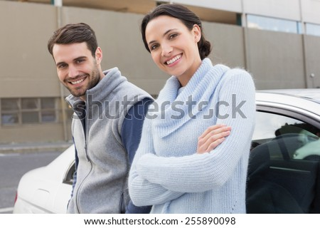 Young couple smiling at the camera outside their car - stock photo