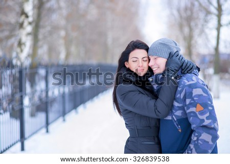 Young couple smiling happily in winter embrace enjoy relationships, loving man and woman in a winter park. Fashion lifestyle vacation in nature, snowy winter day in the city.