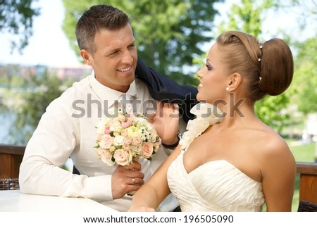 Young couple smiling happy on wedding-day outdoors, looking at each other with love. - stock photo