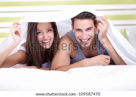 Young couple smiling playing under the sheets in bedroom - stock photo