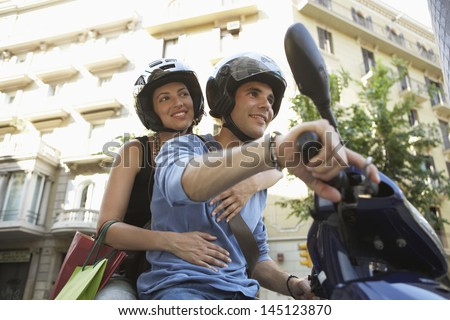 Young couple smiling while enjoying road trip on scooter - stock photo