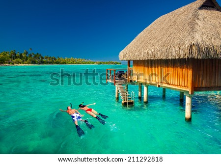 Young couple snorkeling from hut over blue tropical lagoon - stock photo
