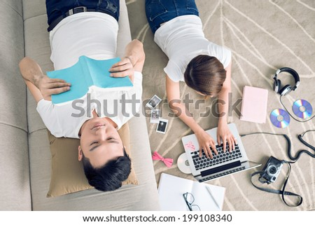 Young couple spending their time at home, view from the top - stock photo