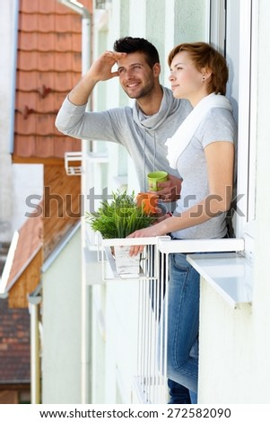 Young couple standing at balcony, having coffee. - stock photo