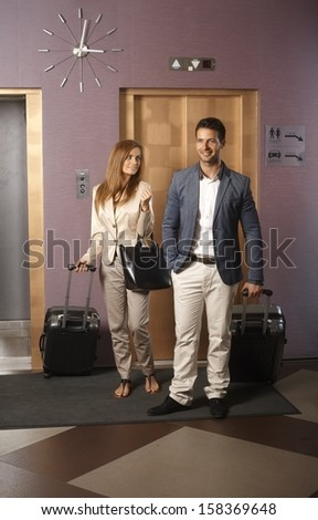 Young couple standing at hotel corridor upon arrival, looking for room, holding suitcases. - stock photo