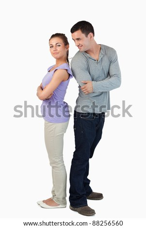 Young couple standing back-to-back to each other against a white backgrounf - stock photo