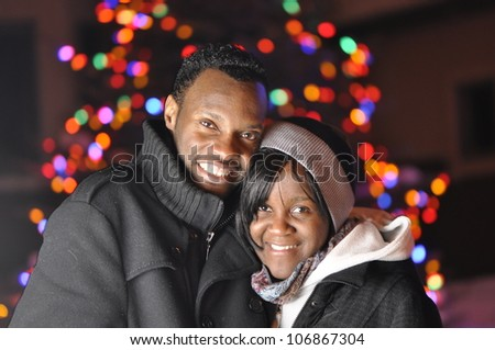 young couple standing in front of the christmas light - stock photo