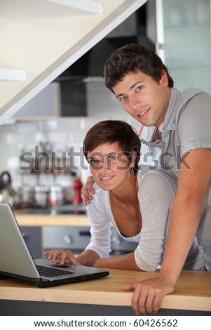 Young couple standing in kitchen with laptop