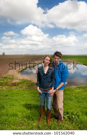 Young couple standing in typical Dutch landscape - stock photo