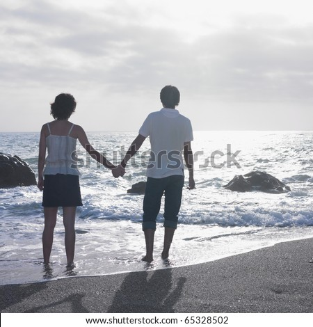Young couple standing in water on beach - stock photo