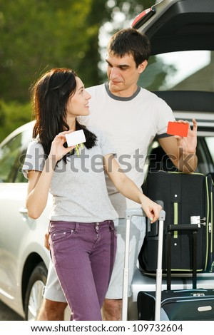 Young couple standing near the opened car boot with suitcases, holding blank credit cards, looking at each other, outdoors - stock photo