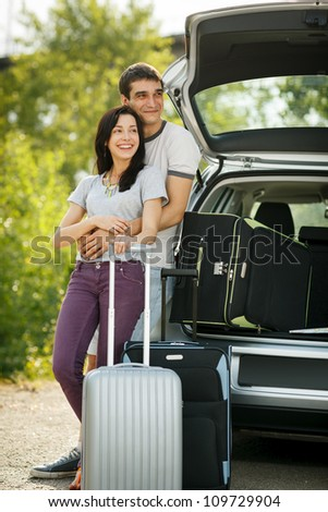 Young couple standing near the opened car boot with suitcases, looking to the side, outdoors - stock photo