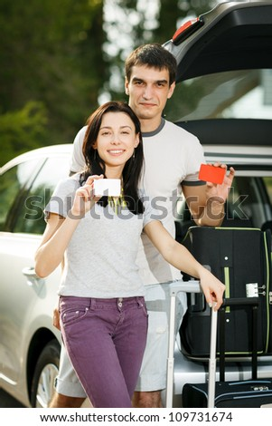 Young couple standing near the opened car boot with suitcases, showing blank credit cards, outdoors - stock photo