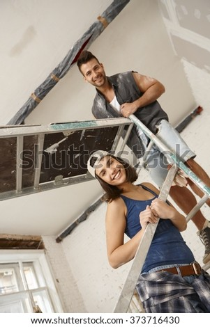 Young couple standing on scaffold, renovating home, smiling happy. - stock photo