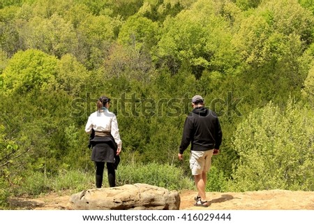 Young couple standing on the bluff top admiring the view; Missouri state parks - stock photo