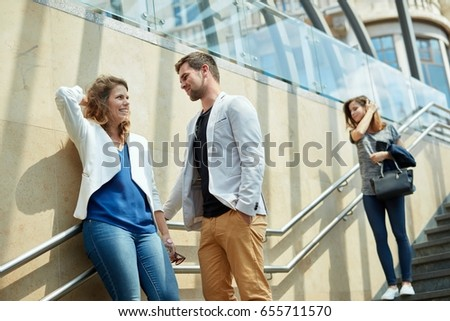 Young couple standing on the stairway of underpass, talking, smiling.