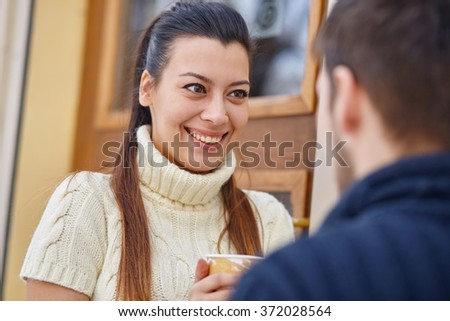 Young couple standing outside the cafe and drinking coffee. - stock photo