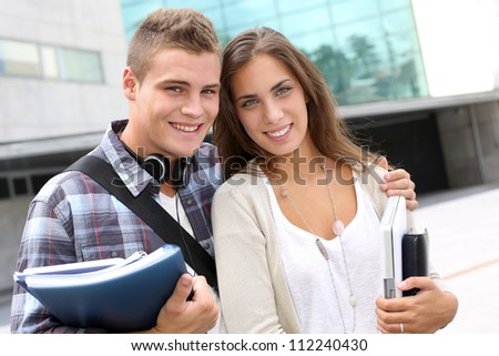 Young couple standing outside the university building - stock photo